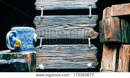 Tea mug in sweater on wood stump. Other stumps in stack. Triple wood sign on the background. Isolated over black