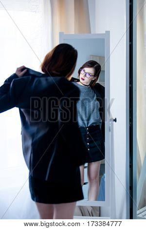 Beautiful Young Woman Standing In Front Of Mirror, Putting On Her Jacket And Looking At Her Reflecti