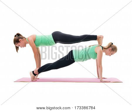 Sporty girls in green tops and leggings training in studio