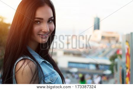 Portrait of a beautiful young sexy Caucasian woman in denim waistcoat at sunset. Make up. Youth, freshness, beauty, romance, happiness concept.