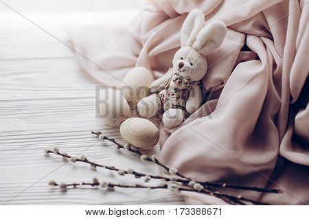 Stylish Easter Bunny Rabit And Eggs And Willow Buds On Rustic Wooden Background And Fabric . Greetin