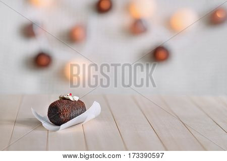 Tasty chocolate cake on a wooden natural background. Top decorated with cream and a piece of jelly. In the background glow round lights. Brown cake is cooking on a white paper.