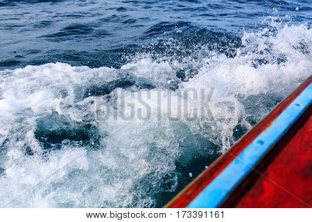 A long tail boat moving in the sea splashing water breaking the waves
