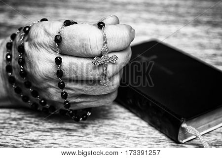 Rosary in old hand and black prayer book. Black and white photography