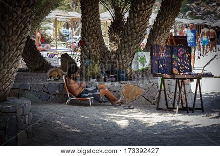 SITIA, CRETE, GREECE - JUNE 2016: Hippie man is laying on sunbeam under palms and selling handmade souveniers