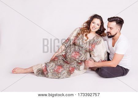 Happy Family. Pregnant Wife Next To Her Husband