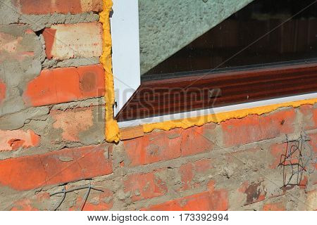 Close up on window insulation with spray foam insulation. Windows installation