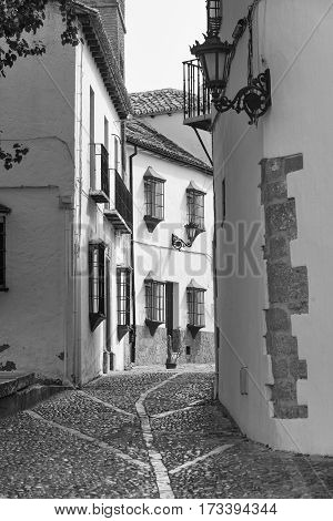 Ronda (Andalucia Spain): old typical street with white houses. Black and white