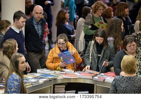 VILNIUS - FEBRUARY 25: Many people choose books at the indoor book market on February 25 2017 in Vilnius Lithuania. Vilnius is the capital of Lithuania and its largest city.
