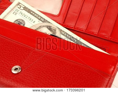 an open, female red purse with five dollars