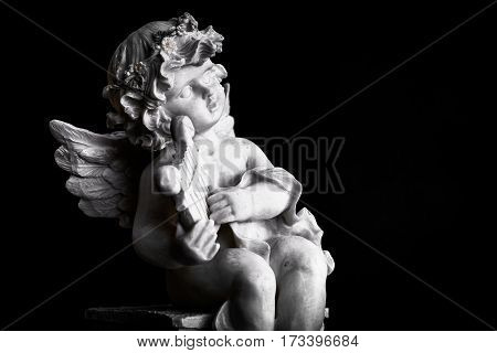 Statue of Little Cupid playing harp in black and white