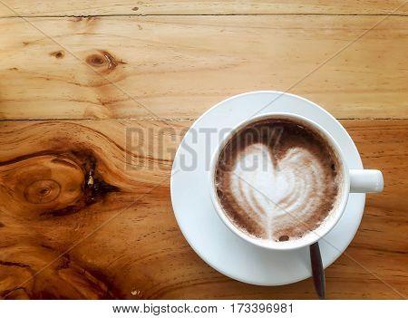 Hot milk latte art coffee on wooden table, Vintage latte art coffee.