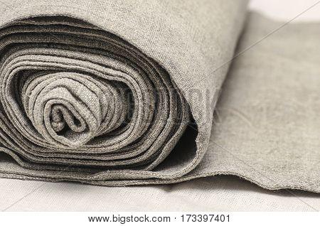 Close up of handmaiden textile canvas in the roll. Homespun hemp unpainted cloth