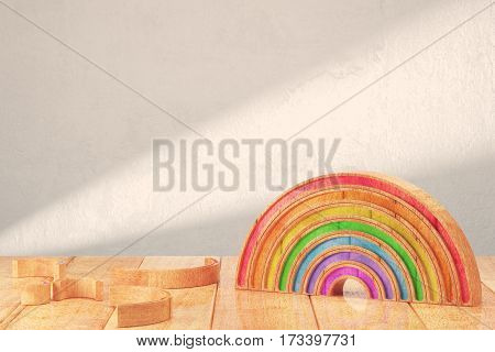 Cartoon styled rainbow on wooden table over bright background. 3d rendering