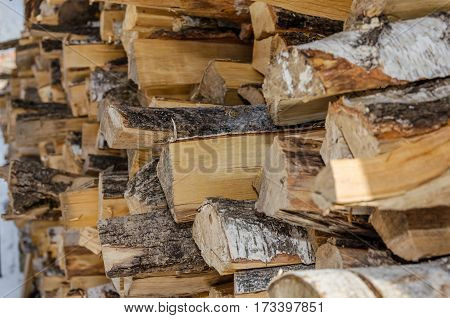 Neatly stacked logs of wood along a wooden wall