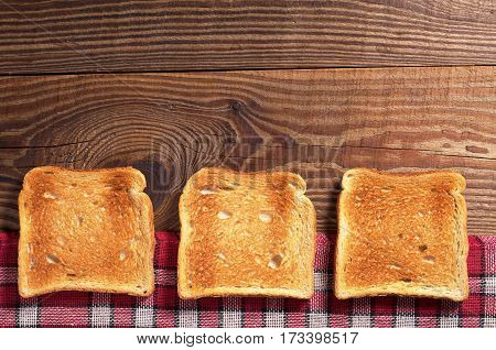 Slices of toasted bread on rustic wooden table top view. Space for text