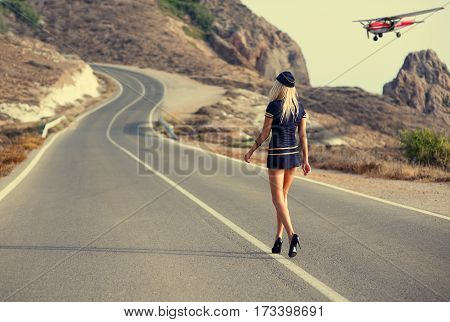 Young, beautiful girl walking along the road to the plane lands
