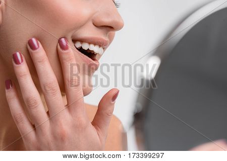 My skin is so smooth. Close up of female face. Joyful girl is touching cheek and laughing