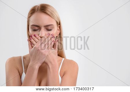 Shy girl is covering her mouth by hands. Her eyes are closed. Isolated. Copy space in right side