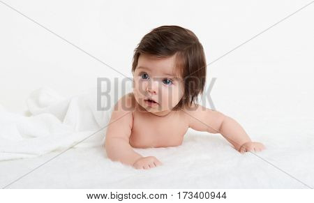Adorably baby lie on towel in bed, white background. Happy childhood and healthcare concept