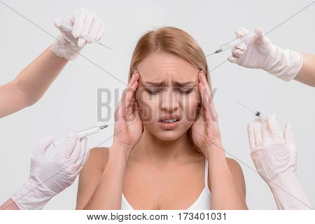 Sad young girl is getting rejuvenating injection. Many doctors are stretching hands with syringes to her face. Female eyes are closed with frustration. Isolated