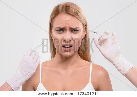 Beauty requires sacrifice. Frustrated young woman is having facial collagen injection. She is standing and looking at camera with despair. Isolated