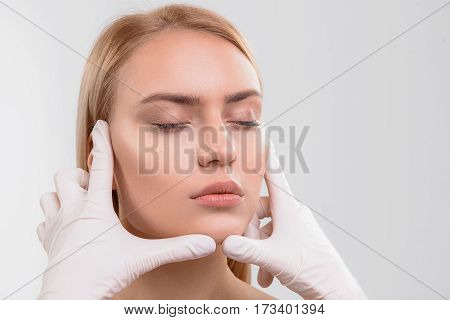 Close up of general practitioner hands checking female skin before plastic surgery. Isolated