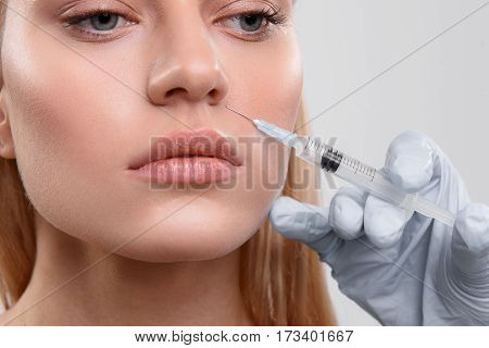 Close up of female face getting botox injection. Doctor holding syringe near nose of woman. Isolated