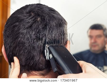 Man getting a haircut by a professional hairdresser using grooming machine. Closeup man having a haircut with a hair clippers. The hands of young barber making haircut to man in barbershop