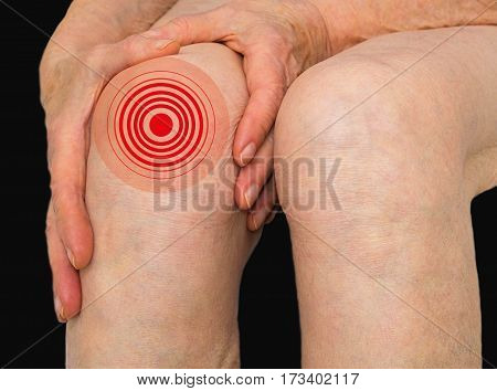 Senior woman holding the knee with pain on gray