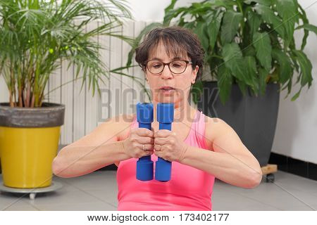 mature woman do exercises with dumbbells indoors