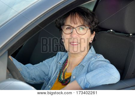 A smiling brunette mature woman driving car
