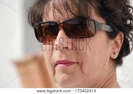 portrait of a brunette mature woman with sunglasses outdoor