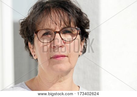 portrait of a brunette mature woman with glasses outdoor