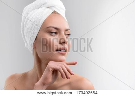 Voluptuous young woman is relaxing after taking shower. She is touching chin by hand with elegance. Lady is standing and looking aside with passion. Isolated and copy space in right side