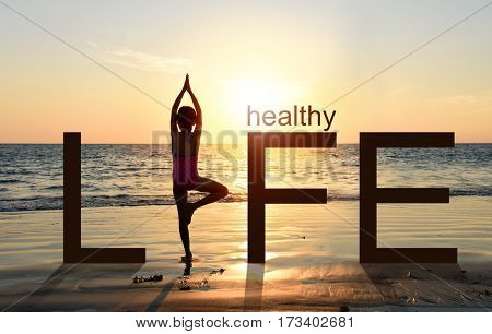 Silhouette of A girl practicing Yoga vrikshasana tree pose on tropical beach with sunset sky background watching the sunset standing as a part of the wording concept for healthy life.