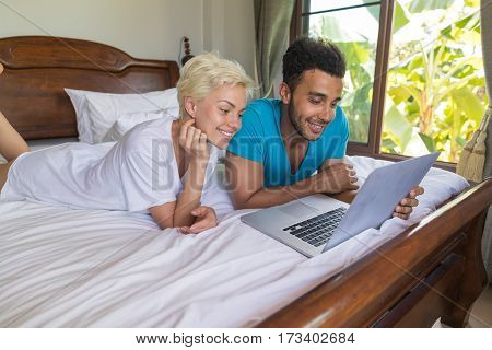 Young Couple Lying In Bed, Happy Smile Hispanic Man And Woman Using Laptop Computer, Lovers In Bedroom