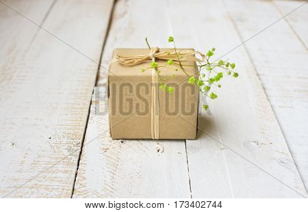 Gift box wrapped in craft paper tied with twine tender small green flower white plank wood background minimalistic copyspace kinfolk