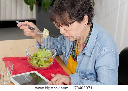 mature woman looking digital tablet while eating a salad