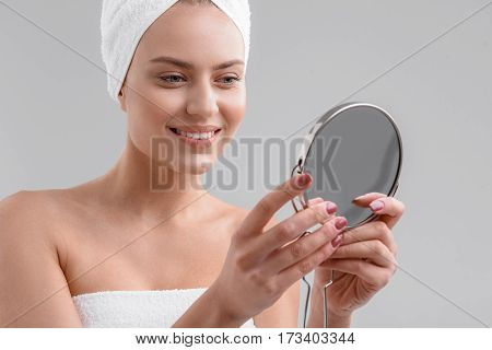 Healthy skin. Happy young girl is observing her face through mirror. She is standing with towel on head and laughing. Isolated