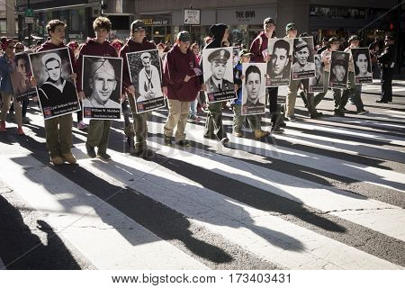 NEW YORK - 11 NOV 2016: Members of Boy Scouts of America carry large posters of servicemen for Keep The Spirit of 45 Alive group in the annual Americas Parade up 5th Ave on Veterans Day in Manhattan.