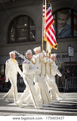 NEW YORK - 11 NOV 2016: Vets in white uniforms from the American Legion Honor Guard carry the American Flag in Americas Parade up 5th Avenue on Veterans Day in Manhattan.