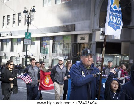 NEW YORK - 11 NOV 2016: A vet carries the banner flag for Operation Mend while marching in Americas Parade up 5th Avenue on Veterans Day in Manhattan.