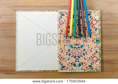 open note book, colored pencils.wooden background.top view
