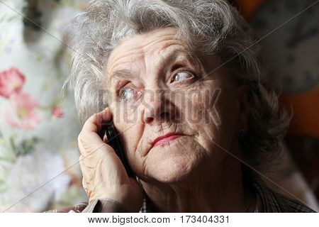 Grandmother with mobile phone on a dark background
