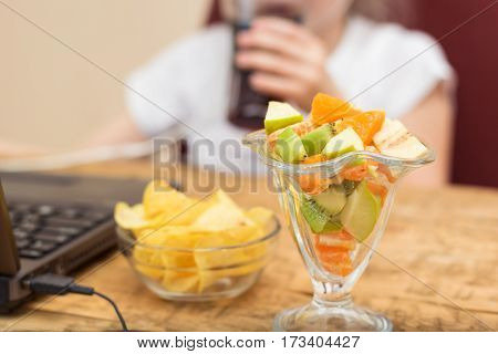 Girl Eats Potato Chips And Fruit Salad In Front Of Laptop.
