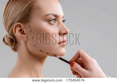 Close up of surgeon hand drawing correction lines on female face before operation. Isolated and copy space in right side