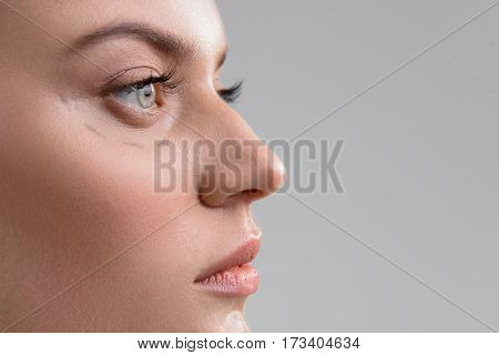 Close up of female face in profile. Calm young woman has correction lines under her eye. Isolated and copy space in right side