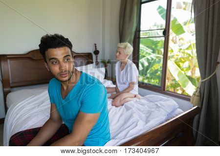 Young Couple Having Conflict Problem, Sad Negative Emotions Hispanic Man And Woman Bedroom Interior