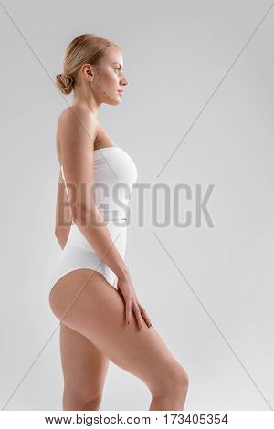 Thin girl is standing in white tight underwear. She is looking forward with aspiration. Correction lines on her face. Isolated